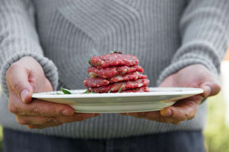 Man is holding burgers for BBQ. Barbecue burgers Standard-Bild