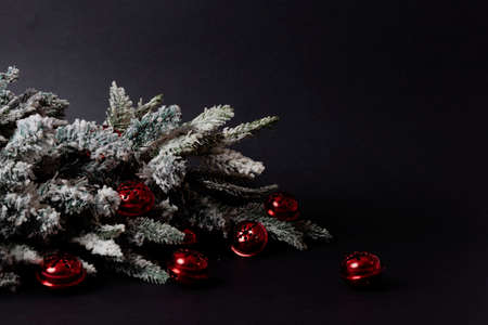 Red Sleigh bells in front of a Christmas tree with snow on black dark Stock Photo