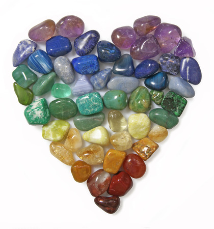 Close up cut out of a Heart shaped using rainbow coloured tumbled Gem Stones on white background