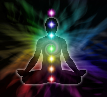 spirituality therapy: Silouette of a man in lotus meditation position with Seven Chakras on flowing rainbow energy background