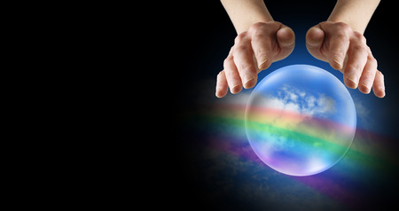 mind body spirit: Clairvoyant hands over crystal ball with rainbow and blue sky on a black banner background