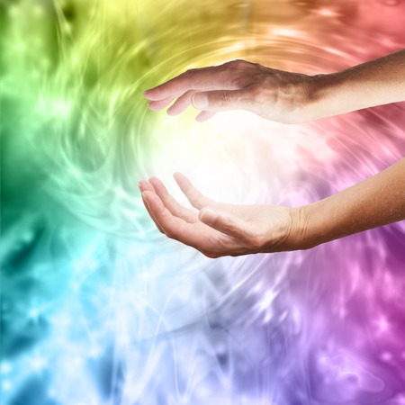 Outstretched healing hands on vivid rainbow vortex swirling energy background Stock Photo