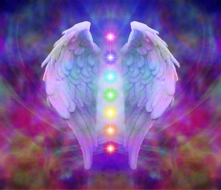 Engelenvleugels en zeven chakra's op kleurrijke achtergrond Stockfoto