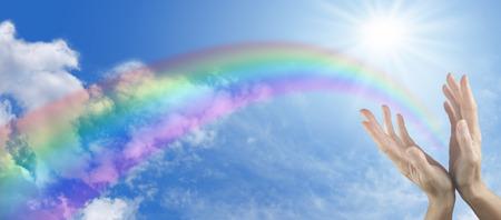 glädje: Panorama blå himmel med sunburst, regnbåge och två händer når upp