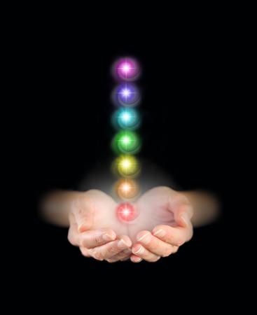 universal love: Manos que salen de la oscuridad, ahuecadas con siete v�rtices Charka Foto de archivo
