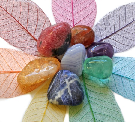 crystals: Close up of Chakra Crystals on coloured skeleton leaves Stock Photo