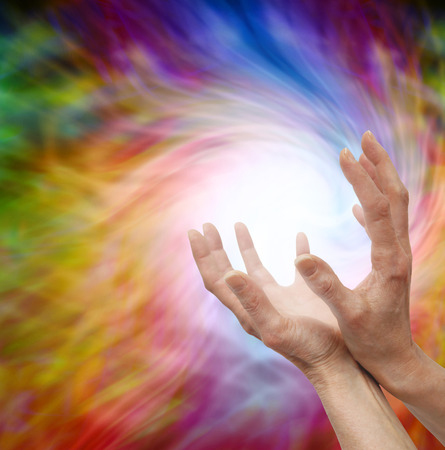 Outstretched healing hands on  vortex swirling energy background Stock Photo