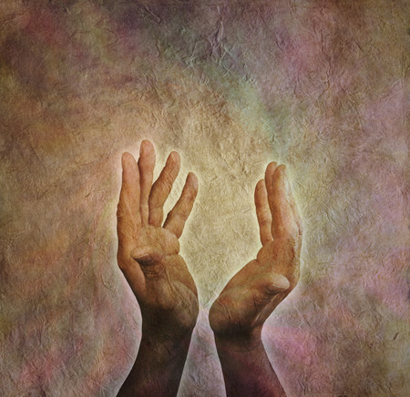 SELF HEALING: Male hands outstretched with parchment aged paper background Stock Photo