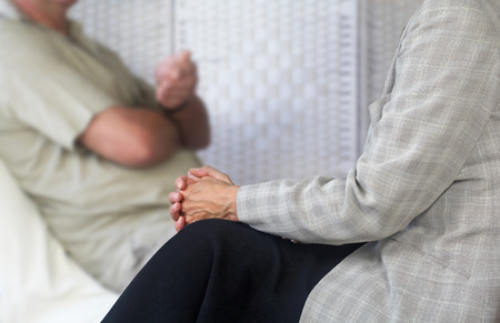 people meeting: Female counselling therapist listening to male patient sat on couch