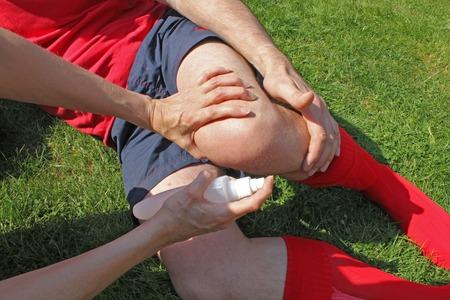 lesionado: Terapeuta atender deportista lesionado en el césped que agarra la pierna