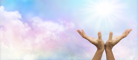Healer s hands outstretched to sunburst with soft multi coloured clouds photo