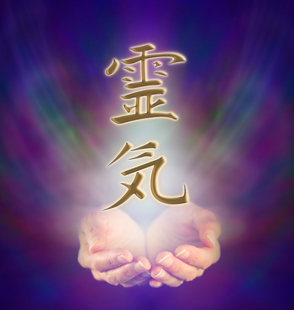 Healers cupped hands and Reiki Kanji Symbol on misty background photo
