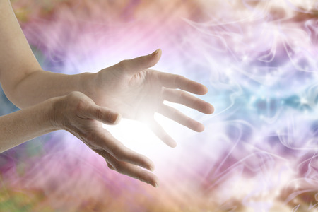 energy healing: Female healing hands and vibrant energy field Stock Photo