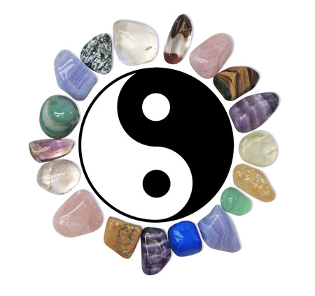 Circle of healing crystals around Yin Yang symbol on white background
