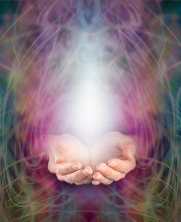 Healers cupped hands and energy manifestation Stock Photo