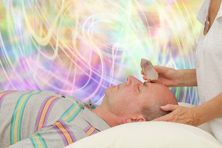 Balancing Third Eye Chakra with terminated quartz Stock Photo