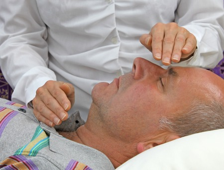 Female healer channeling healing to male patient photo