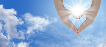 holistic:   Hands holding the sunshine and create heart shape