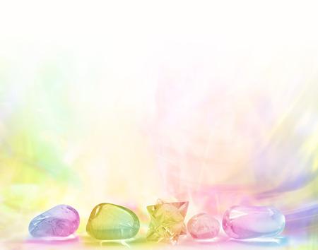Rij van Rainbow Healing Kristallen op een pastelkleurgradiënt regenboog gekleurde achtergrond Stockfoto