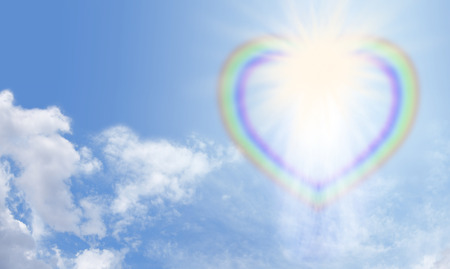 Heart rainbow bursting with light on a blue sky