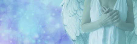 left hand: Cropped Angel showing torso in white robes with hands held over heart on a misty blue bokeh with copy space on left hand side Stock Photo