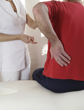 healing practitioners: Sportsman with back injury seeking advice from specialist Stock Photo