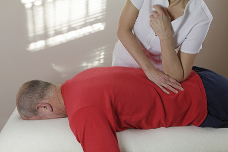 treat acupressure: Massage therapist pressing elbow into sportmans QL muscle Stock Photo