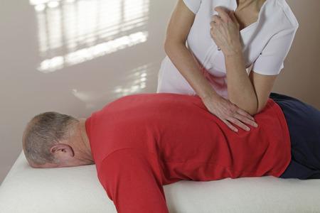 codo: Terapeuta de masaje presionando el codo en el músculo QL del deportista