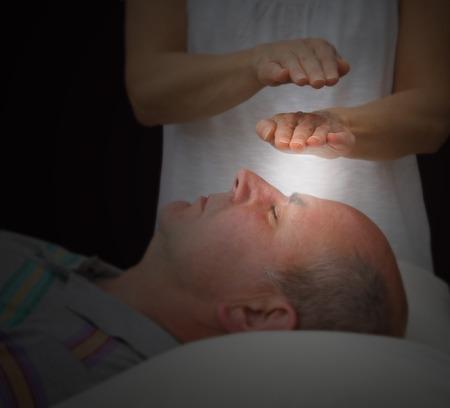 Healer sensing aura levels over third eye chakra photo