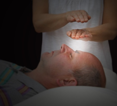 complementary therapy: Healer sensing aura levels over third eye chakra