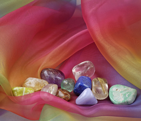 Chakra Gemstones on Rainbow Chiffon Material Background