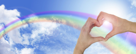 healing hands: Heart hands on wide arcing rainbow blue sky background Stock Photo