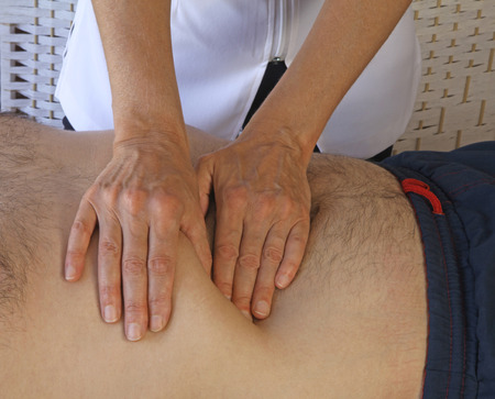Practitioner giving male an abdominal examination photo