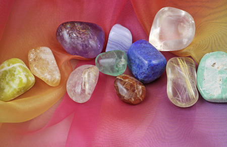 crystals: Chakra healing gemstones on Rainbow Chiffon Material Background