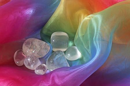 tumbled: Clear Quartz tumbled gemstones on Rainbow Chiffon Material Background Stock Photo