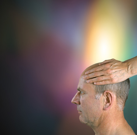 Male patient receiving golden healing energy through crown photo