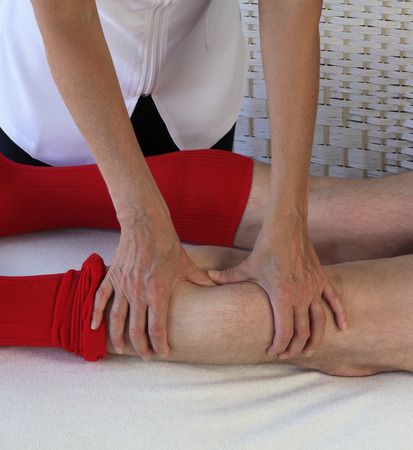 treat acupressure: Sports massage therapist applying pressure to gastrocnemius muscle