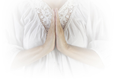 worshiper: Female with hands in front in prayer position wearing a white robe