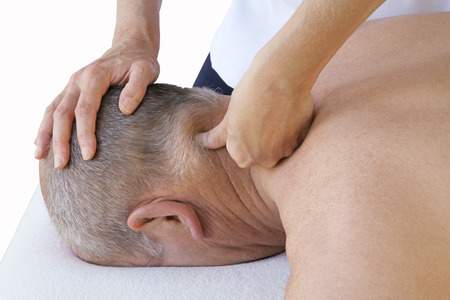 Massage Therapist applying pressure to posterior cervical Stock Photo