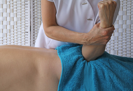 treat acupressure: Female Therapist applying elbow pressure into gluteal muscle Stock Photo