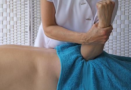 masaje deportivo: Mujer terapeuta aplica presión codo en el músculo glúteo