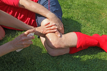 female therapist: Injured sportsman lying on grass clutching leg with female therapist attending to injury Stock Photo