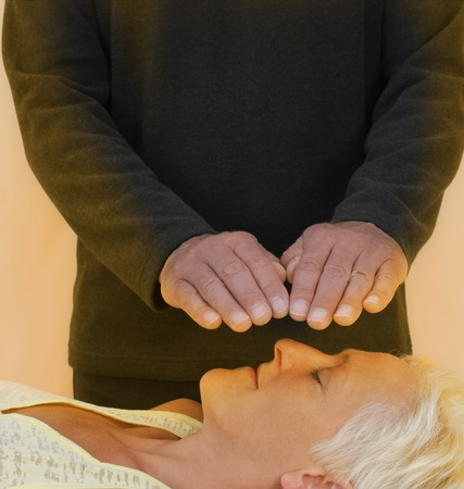 healer: Male healer and female client bathed in golden healing energy field Stock Photo