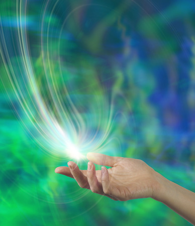 Spirit Release  Female open hand with a white energy formation floating above on an ethereal green and blue background and plenty of copy space