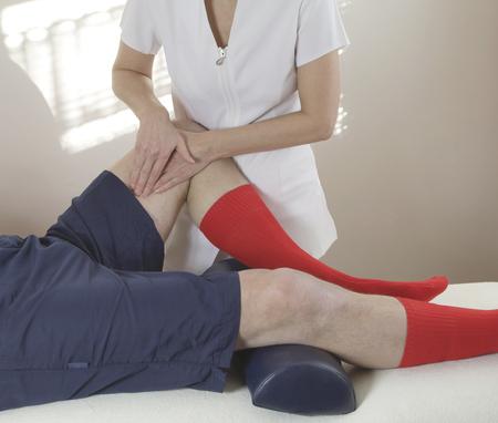 masaje deportivo: Deportes femenino terapeuta de masaje que trabaja en la cara interna del muslo femenino del músculo terapeuta de masaje deportivo que trabaja en el músculo del muslo interno del cliente masculino al tiempo que sienta en el sofá con la luz que entraba por las persianas de la ventana en el fondo Foto de archivo