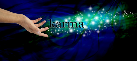 karmic: Creating Karma  Female hand outstretched with the word Karma floating away amongst a stream of sparkles on a dark blue swirling background with a swirl of green light behind the glitter