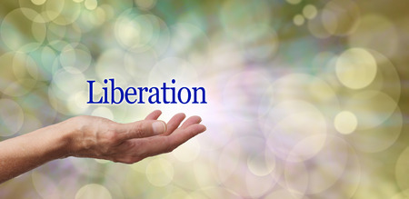 liberate: Celebrate Liberation  Female hand outstretched with the word Liberation floating above on a neutral toned bokeh effect background
