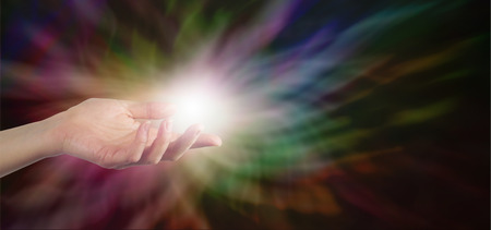 Female Healer with hand out palm up with a ball of white energy appearing to manifest on a dark rainbow colored energy formation background banner with plenty of copy space