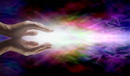 universal enlightenment: Beaming Reiki Healing Energy  Male parallel hands with a beam of bright white energy outwards  on a vibrant multicolored ethereal energy formation background
