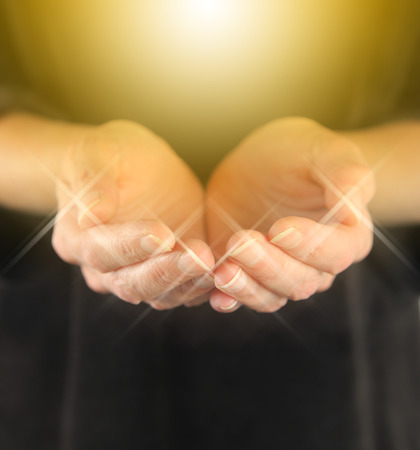 Healer with Golden Healing Orb Energy  female holding hands in cupped position with a bright golden orb  energy hovering above and sparkles around finger tips